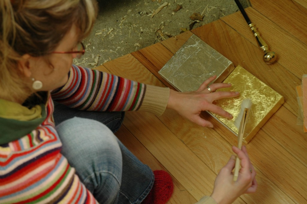 Applying gold leaf in the studio.